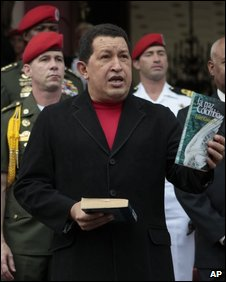 President Chavez holds a bookd called Peace in Colombia by Fidel Castro in file photo from 6 August 2009