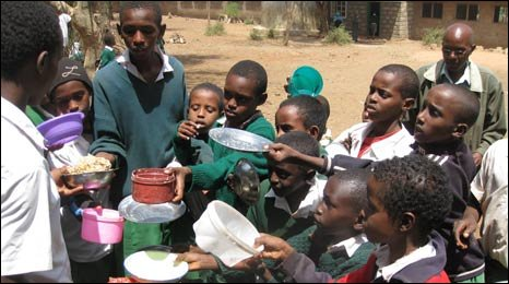 Children gather at the lunch pot for more food, St Kizito Primary School, Kenya