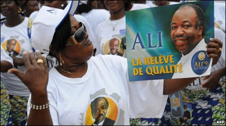 A woman holds up a poster of Ali Bongo Ondimba