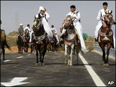 Ceremonial horsemen ride a stretch of the first part of the highway