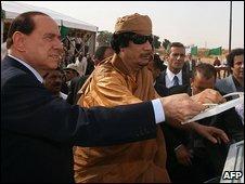 Italian PM Silvio Berlusconi and Libyan leader Muammar Gaddafi lay a foundation stone for a coastal highway
