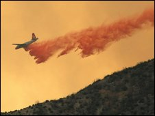 Flame retardant is dropped from a plane above forest near Los Angeles, 30 August, 2009