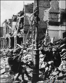 Young boys swinging from a lamp post in the midst of rubble left by a city bombing raid. Circa 1943