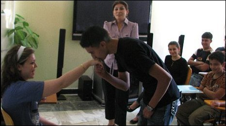A young man kisses a girls' hand in a classroom