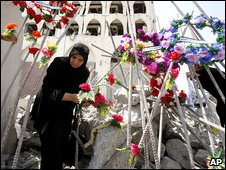 A woman places flowers in front of the Iraqi Foreign Ministry which was targeted in August