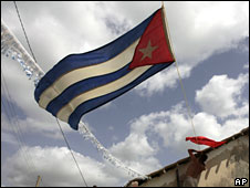 A resident decorates his house with a Cuban flag in Holguin, north-east Cuba, 25 July 2009