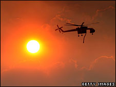 A firefighting helicopter flies by a the sun, as it prepares to drop water in Glendale, California.