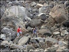Villagers walk among rocks from landslide triggered by earthquake in West Java, Indonesia, 3 September 2009