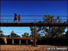 Two aboriginal girls walk across a foot bridge above the dry Todd River on August 24, 2009 in Alice Springs
