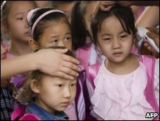 Chinese children have their temperature taken