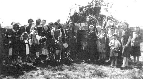 Image of VE Day bonfire at Thistleboon, Mumbles, with placard proclaiming 'the end of evil'.