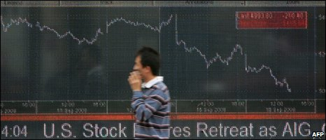 Man walks past shares board on 16 September 2008
