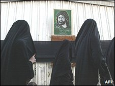 Saudi Shia women walk past a portrait of Imam Hussein in Qatif