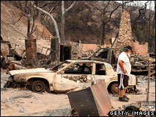 A man looks at a burnt-out home and car, 2 Sept