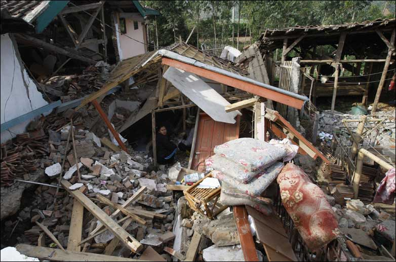 Residents clean up rubble at a house destroyed by an earthquake