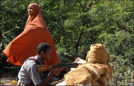 A woman walks past a Somali Islamist fighter on patrol in a street in Mogadishu