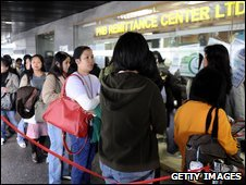 Filipino domestic helpers line up to send money home at a remittance centre in Hong Kong
