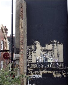 Banksy mural surrounded with paint