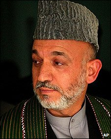Hamid Karzai wearing a cape and karakul hat
