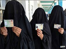 Burqua-clad women hold their identification cards as they prepare to vote
