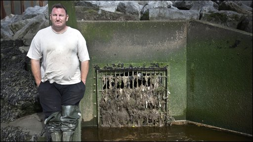 Robert Griffith standing next to a Combined Sewer Overflow in Burry Inlet, South Wales