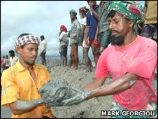 Locals repair a breach in the sea defences around Gabura island, south Bangladesh