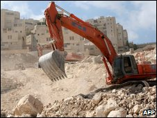 A bulldozer clears rocks at the construction site of new housing units in the Israeli settlement of Har Homa, East Jerusalem