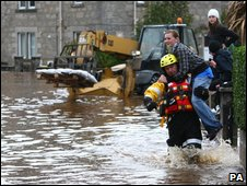 A resident is evacuated from her house after the River Lossie burst in banks in Elgin.