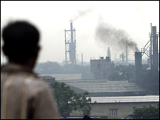 A bystander watches as smoke rises from a cast iron factory at Howrah on the outskirts of Kolkata, India, in July 2008