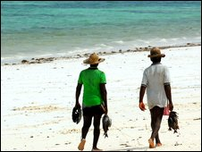 Men walking a Zanzibar beach