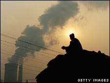 A man squats on the truck goods near a power plant emitting plumes of smoke from industrial chimneys in Beijing, China. File photo