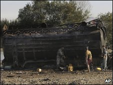 Troops inspect the site where villagers reportedly died when US jets bombed fuel tankers hijacked by the Taliban, at Kunduz, on 5 September 2009
