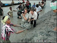 BBC reporter and cameraman filming locals working on sea defences, south Bangladesh