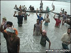 Men working on sea defences at Gabura Island wave goodbye to BBC reporter, south Bangladesh