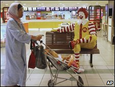 A Malaysian with her baby walks in front of a McDonald's outlets in Kuala Lumpur