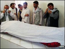 Afghan men weep over the body of Afghan journalist Sultan Munadi at a hospital in Kunduz province on 8 September 2009
