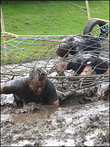 Competitors in a muddy obstacle
