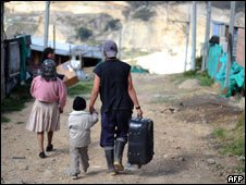 A family walks along the street of Altos de la Florida shantytown