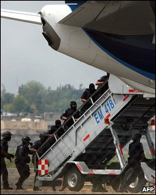 Police enter from rear of plane
