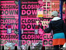A shop window covered in posters advertising a closing down sale