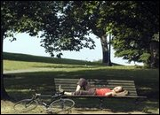 A man enjoys a snooze next to his bicycle on a park bench