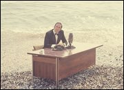 John Cleese sitting at a desk on the beach from 'now for something completely different' sketch
