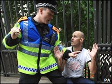 An EDL supporter is held at baton-point by a police officer
