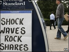 Newspaper billboard reports another tumultuous day on the stock market