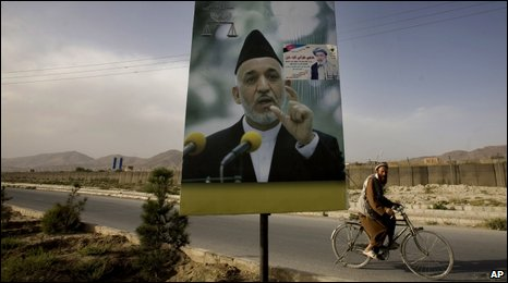 An Afghan man cycles past an election poster of Hamid Karzai