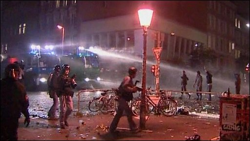 Water cannon and protesters