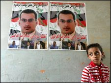 A relative of Muntadar al-Zaidi stands beneath his poster