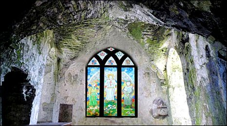 Image of the chapel shows a stained glass window, with a small cupboard in the rock to the left and a holy water font to the right of it.