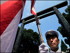 A man dressed in the uniform of the Imperial Japanese Navy waves a flag at Yasukuni Shrine on 15 August 2009