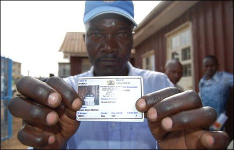 Man holds up ID card in Kibera